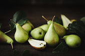 Closeup of a freshly picked pears with half slice. Harvested pears on wooden table.