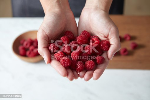 Natural fresh home grown fruits in the girls' hands. Ingredients for delicious desserts on kitchen table. Concept healthy food.