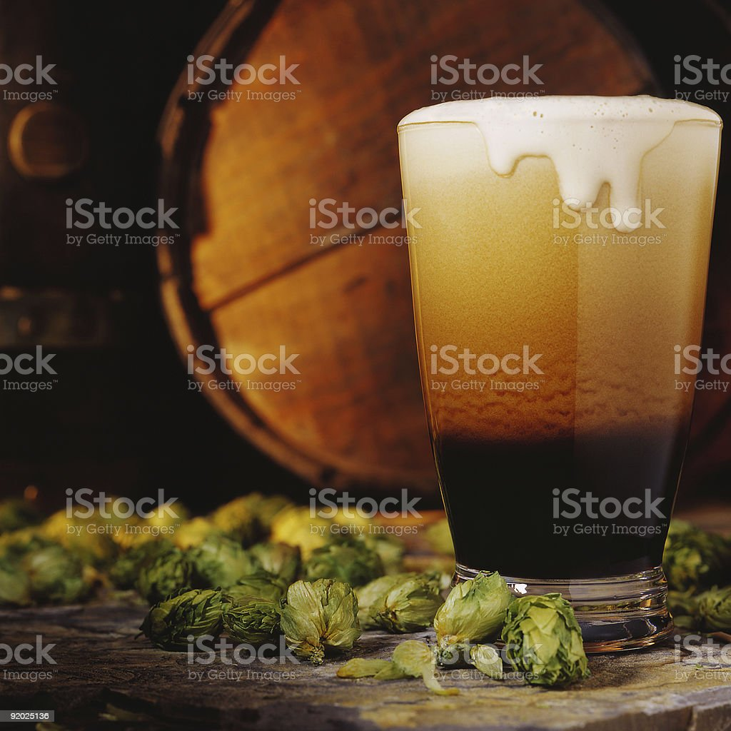 Freshly poured stout beer cascading with hops. royalty-free stock photo