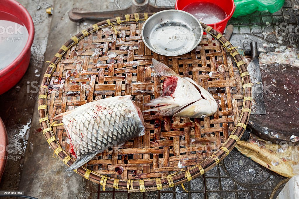 Freshly prepared fish Freshly slaughtered fish placed at a woven tray at a fishmongers street shop in Hanoi, Vietnam. Animal Scale Stock Photo