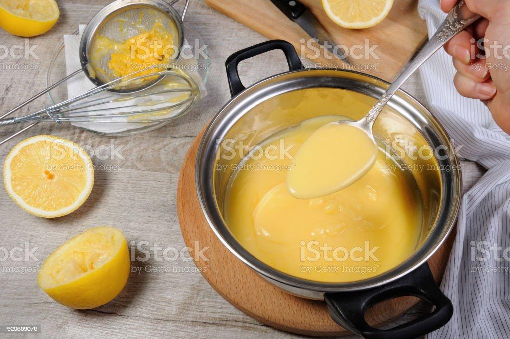 Freshly prepared lemon kurd - custard on fruit juice, in a saucepan stir with a spoon stock photo