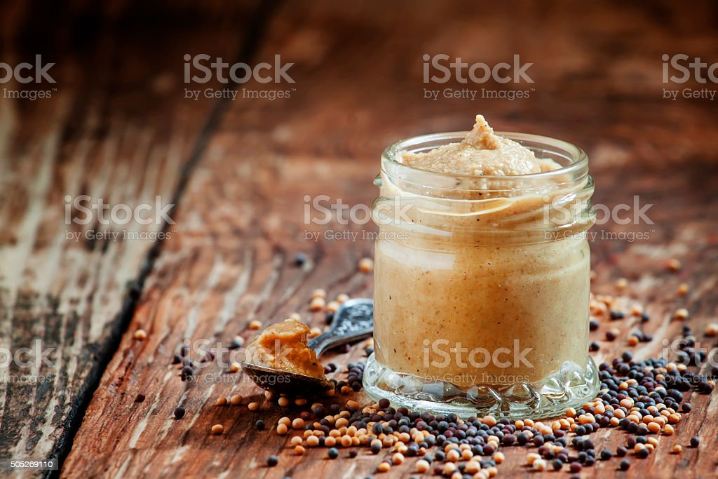 Freshly prepared mustard sauce in a small glass jar stock photo