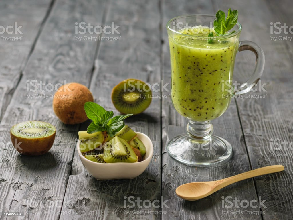 Freshly prepared smoothie of kiwi, Apple, mint and kiwi slices on the rustic table. royalty-free stock photo