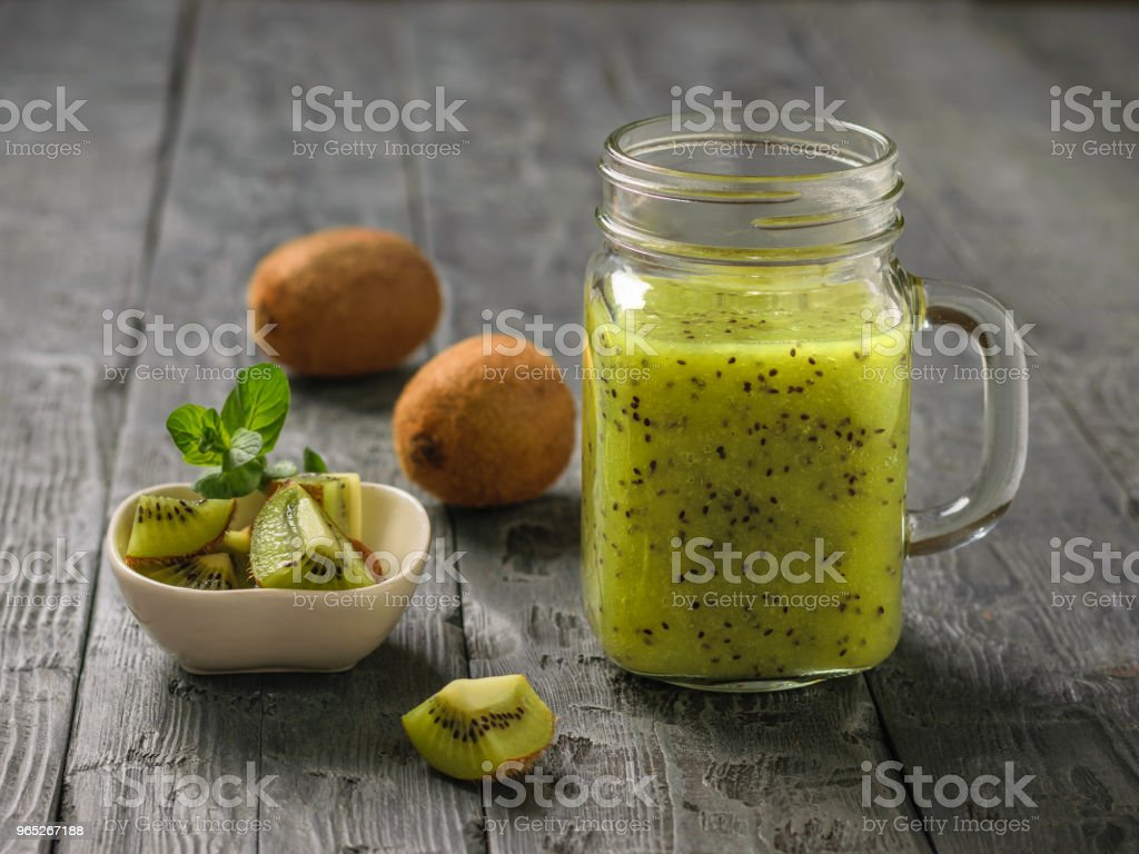 Freshly prepared smoothie of kiwi, Apple, mint and kiwi slices on the black rustic table. royalty-free stock photo