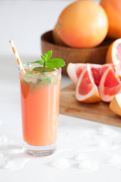 freshly pressed grapefruit juice with mint leaves and ice on white table close up - grapefruit cocktail stock photos and pictures