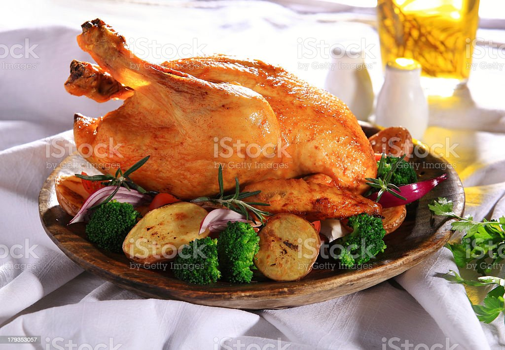 A freshly roasted chicken with vegetables stock photo