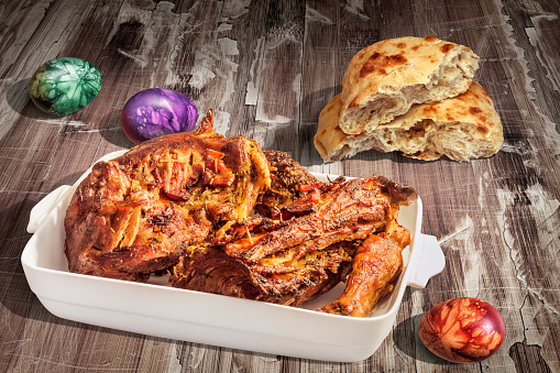istock Freshly Spit Roasted Lamb Shoulder Served With Traditional Leavened Flatbread And Hand Painted Easter Eggs On Rustic Old Lacquered Weathered Cracked Flaky Wooden Background 1044234256