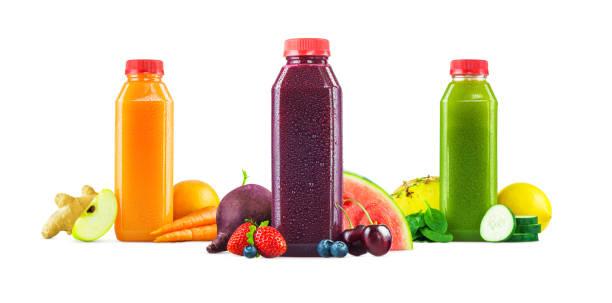 fruits frais pressés et bouteilles de jus de légumes sur fond blanc - jus de fruit photos et images de collection