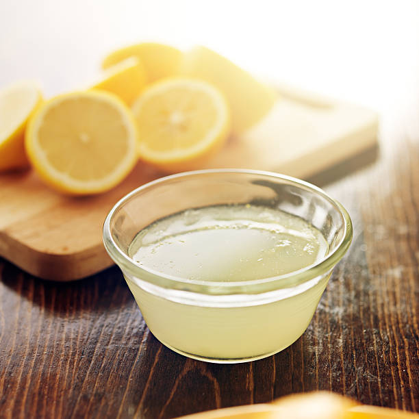 freshly squeezed lemon juice in small bowl freshly squeezed lemon juice in small bowl shot close up lemon juice stock pictures, royalty-free photos & images
