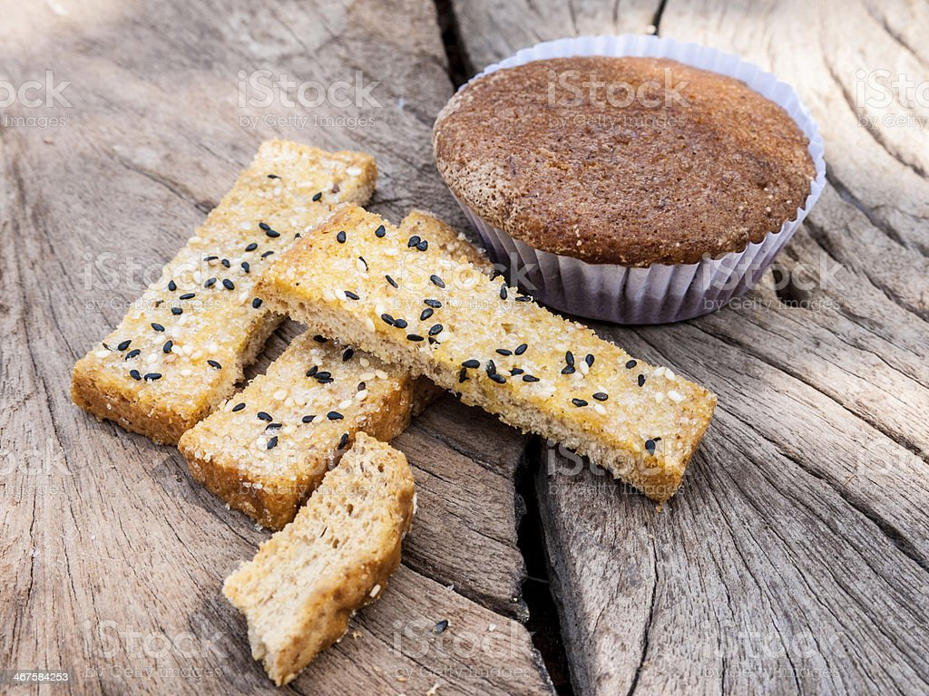 Freshly toasted  sesame bread and banana cupcake on wood royalty-free stock photo
