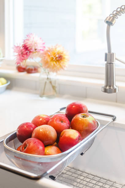 Freshly washed apples in a strainer rack in sink. Vertical. Modern Farmhouse style, dahlias in background. High Key. Plenty of copy space. stock photo