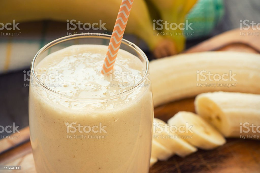 Fresh-made glass of banana smoothie with straw on wood stock photo