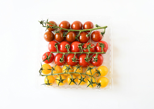 Freshness bunch of mix dark -orange, yellow-gold and red cherry-grape tomato with green branch on white background. Food nature sweet taste and  low acid .Vegetarien and appetizer idea.