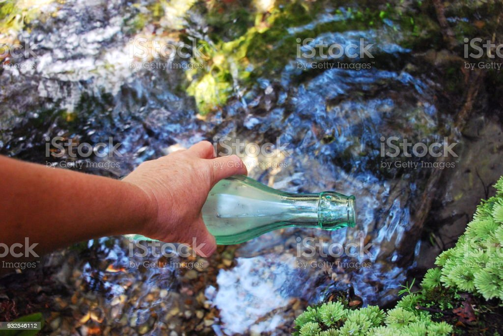 Freshwater Water Concept; Glass Water Bottle with River Background