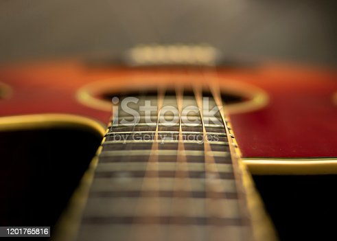 Shot from the neck of the acoustic guitar with focus on the fifteenth fret