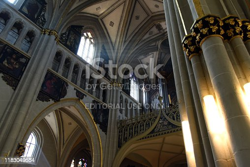 Fribourg Cathedral  is a Roman Catholic cathedral in Fribourg, Switzerland, built in the Gothic style, on a rocky outcrop 50 metres above the river Sarine (Saane). The Image shows an inside view of the beautiful gothic building with some sunbeams.