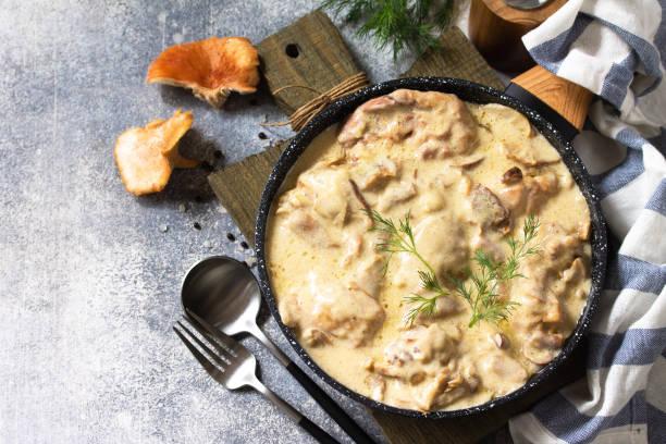 프리카스 - 프랑스 요리. 닭고기는 버섯을 곁들인 크리미한 소스에 가벼운 돌 을 배경으로 팬에 삶습니다. 공간을 복사합니다. 스톡 사진