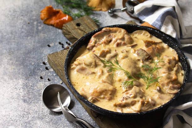 프리카스 - 프랑스 요리. 닭고기는 버섯을 곁들인 크리미한 소스에 가벼운 돌 을 배경으로 팬에 삶습니다. 스톡 사진