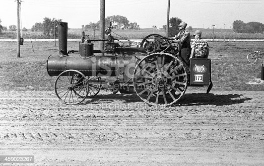 Cedar Falls, Iowa, USA - August 23, 1958: Frick steam traction engine being driven in the Threshermen's Field Days parade. A steam engine like this would have been used to power a threshing machine or other farm machinery. Although steam engines and steam tractors were used in the US until the late 1930s and early 40s, collector goups were already forming by the time this photo was taken in 1958 to preserve steam engines and tractors.