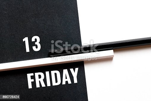 istock friday 13, monochrome concept with paper sheets and pencils 890726424