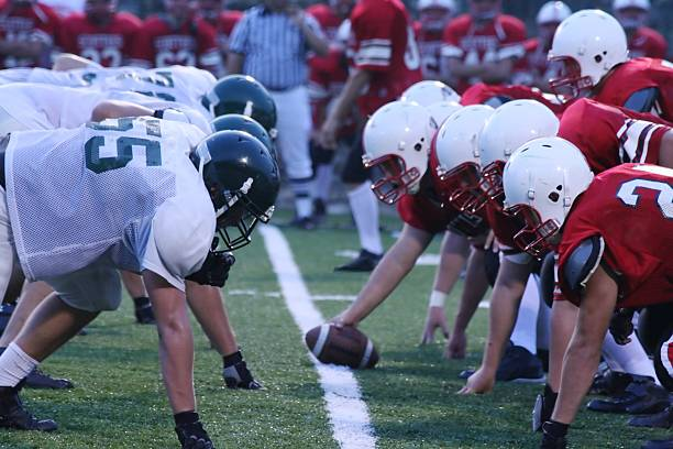 Friday Night Football High school football teams ready for action line of scrimmage stock pictures, royalty-free photos & images