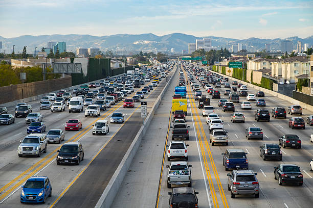 Friday Traffic on the 405 freeway North Los Angeles California Los Angeles, CA, USA - January 22th, 2016: A northbound view of the 405 freeway during Friday afternoon traffic with Getty Museum, Westwood and Santa Monica mountains in the background.   westwood neighborhood los angeles stock pictures, royalty-free photos & images