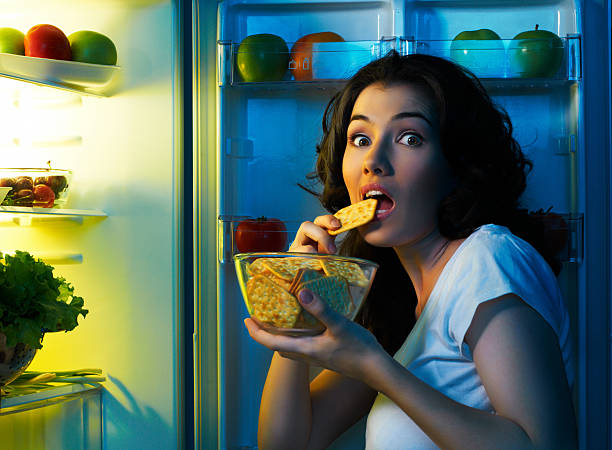 fridge with food a hungry girl opens the fridge midnight stock pictures, royalty-free photos & images