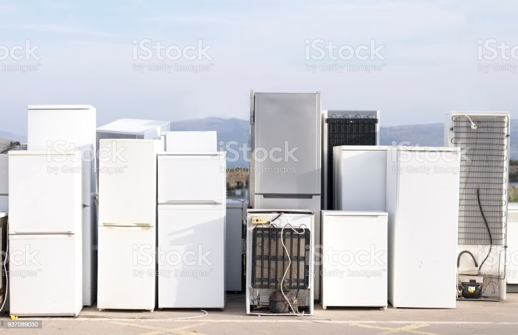 Fridges stacked in a row for recycle used refrigeration units pollution gas stock photo