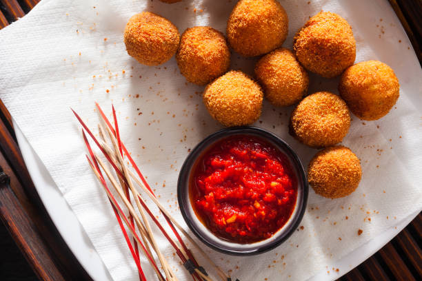 Fried Arancini rice balls . Typical Sicilian street food with spicy sauce stock photo