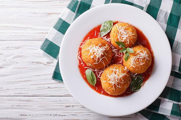 fried arancini rice balls with tomato sauce. horizontal top view stock photo