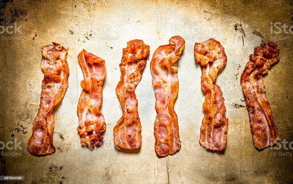 Fried bacon. On old rustic background. foto royalty-free