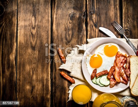 istock Fried bacon with eggs and orange juice. 837067198