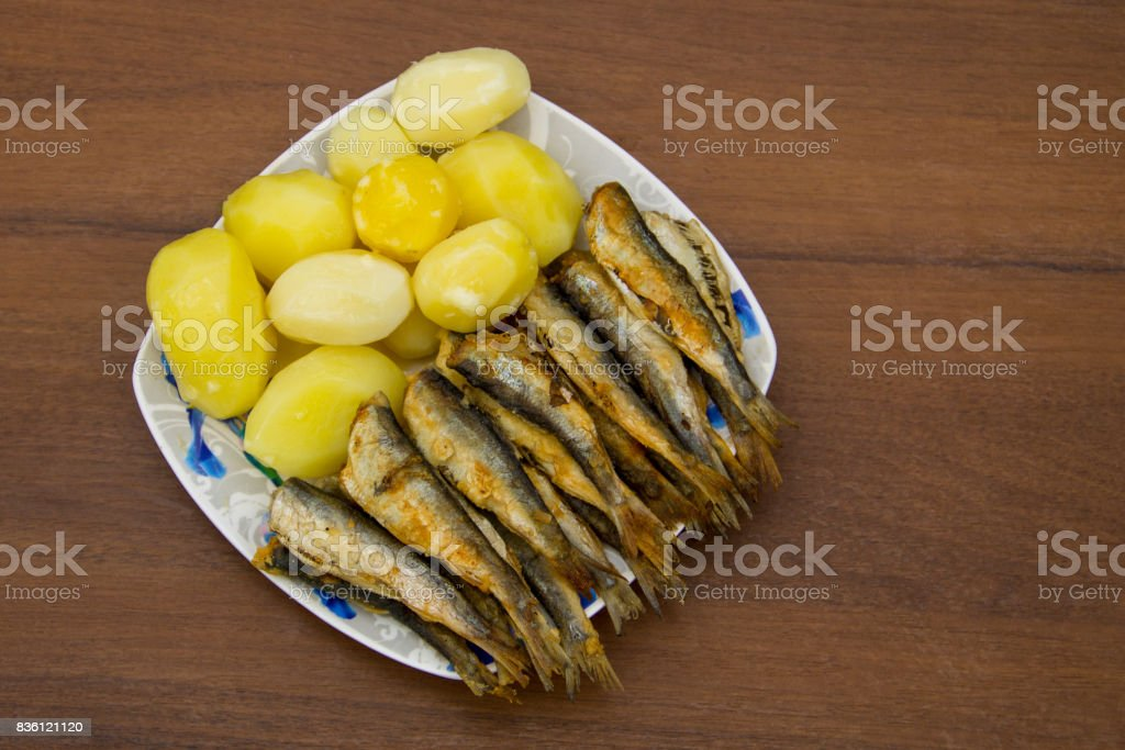 Fried baltic herring with boiled potatoes on a plate on wooden background stock photo