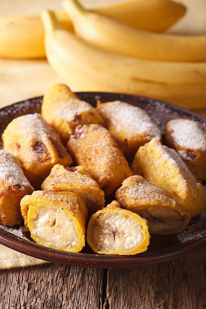 Fried bananas sprinkled with powdered sugar close-up. Vertical - foto de acervo