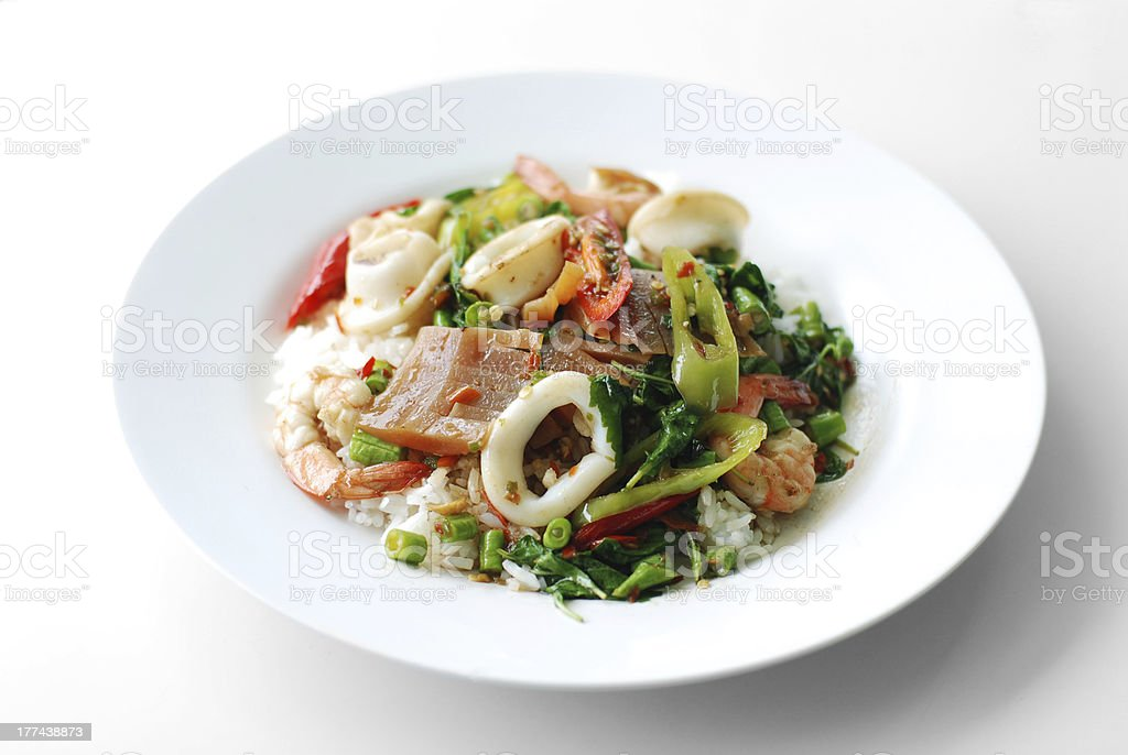 Fried basil leave with squid, shrim on cooked rice stock photo