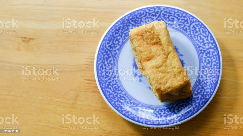 Fried bean curd in blue chinese dish on wooden table stock photo