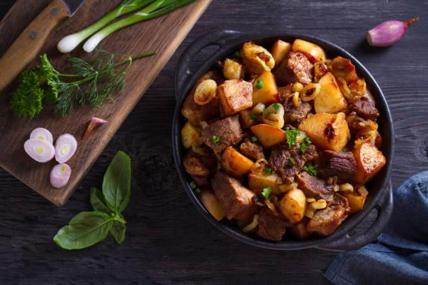 Carne frita y patatas con cebolla y ajo - foto de stock