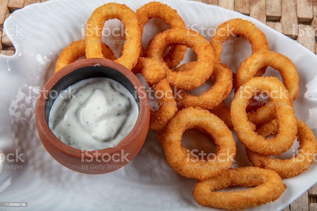 Fried Breaded Onion Rings With Sauce On Wooden Board