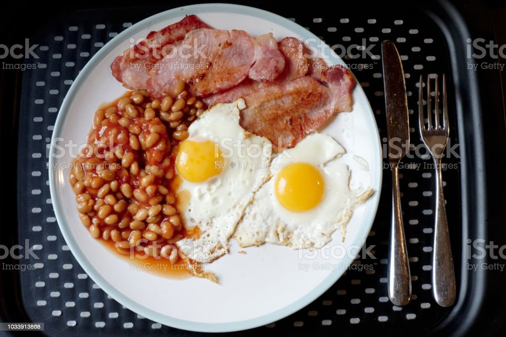 Fried breakfast view from above of bacon beans and eggs on plate and tray stock photo