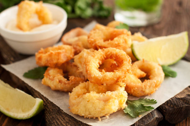 fried calamari rings on wooden cutting board - жареный стоковые фото и изображения