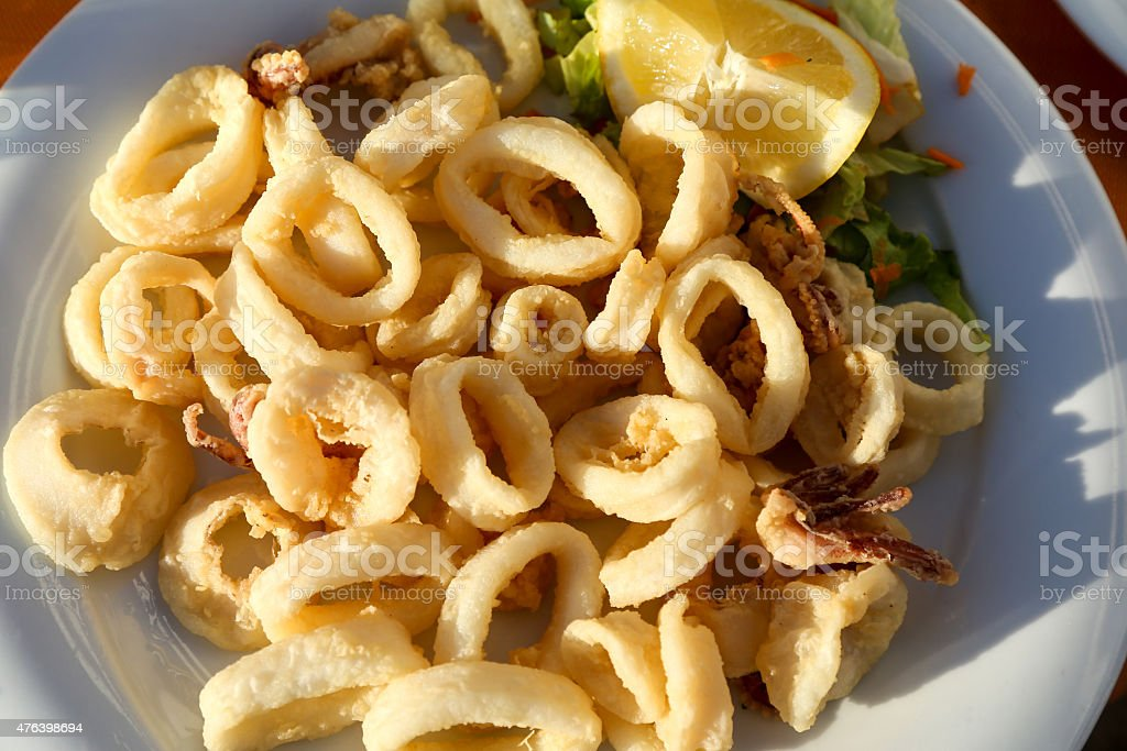 Fried calamari rings with lemon stock photo