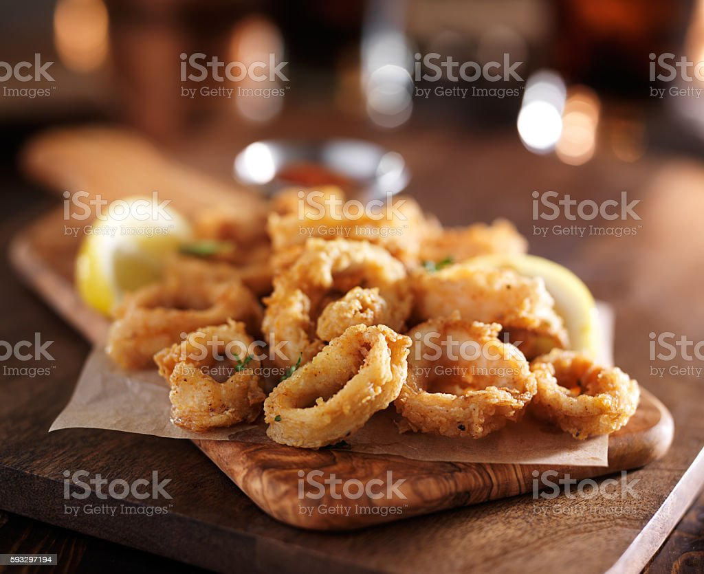 fried calimari rings on wooden tray with dipping sauce stock photo