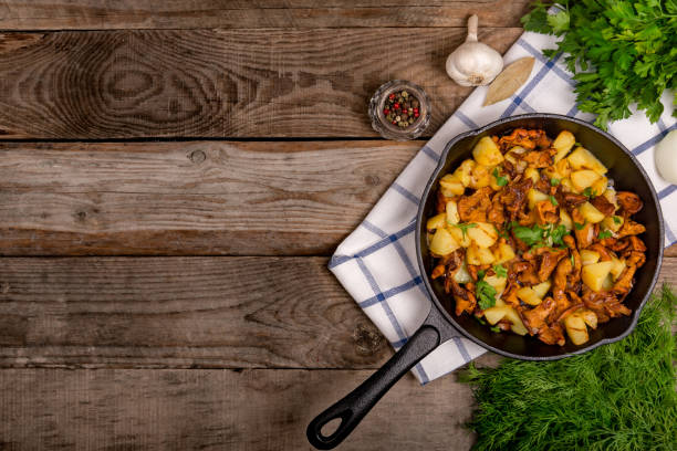 fried chanterelle mushrooms with potatoes onion and parsley in a frying pan and the ingredients on the table. horizontal top view close-up stock photo
