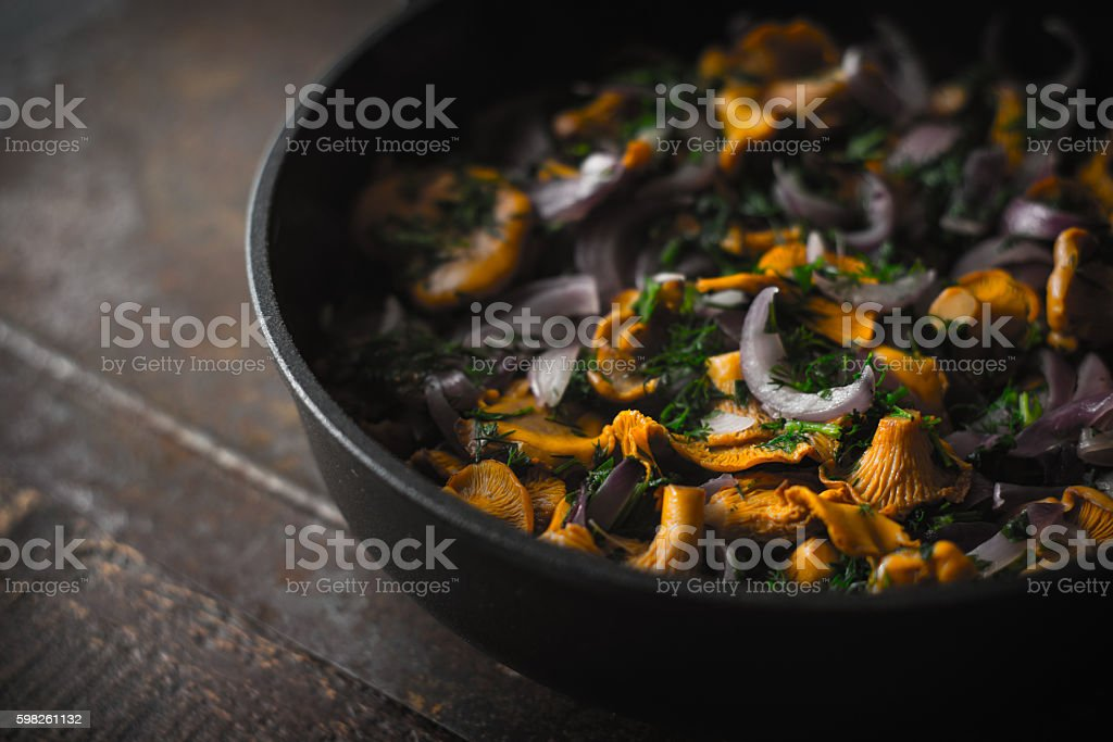 Fried chanterelles with dill in the pan  horizontal stock photo