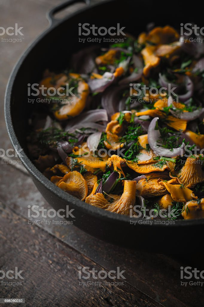 Fried chanterelles with dill in the pan vertical stock photo