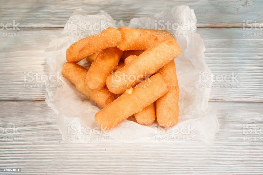 Fried cheese sticks in paper on white wooden table stock photo