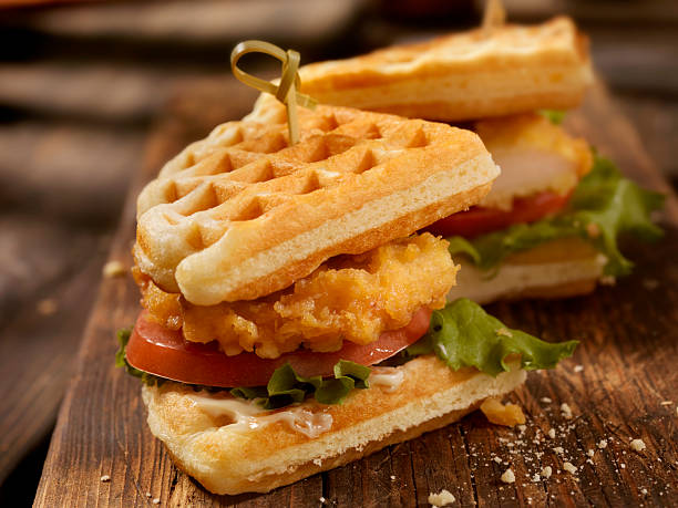 Fried Chicken and Waffle Sandwich Fried Chicken and Waffle Sandwich with Lettuce and Tomato-Photographed on Hasselblad H3D2-39mb Camera waffle stock pictures, royalty-free photos & images