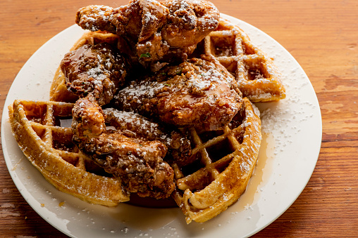 Fried chicken and waffles with berry butter and crispy southern fried chicken. Classic American breakfast or brunch favorite. Homemade waffles served with butter and maple syrup.