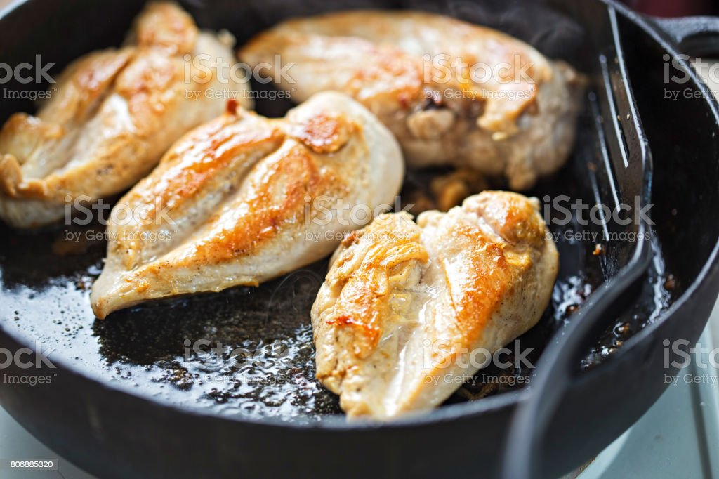Fried chicken breasts on vegetable oil, iron cast pan stock photo