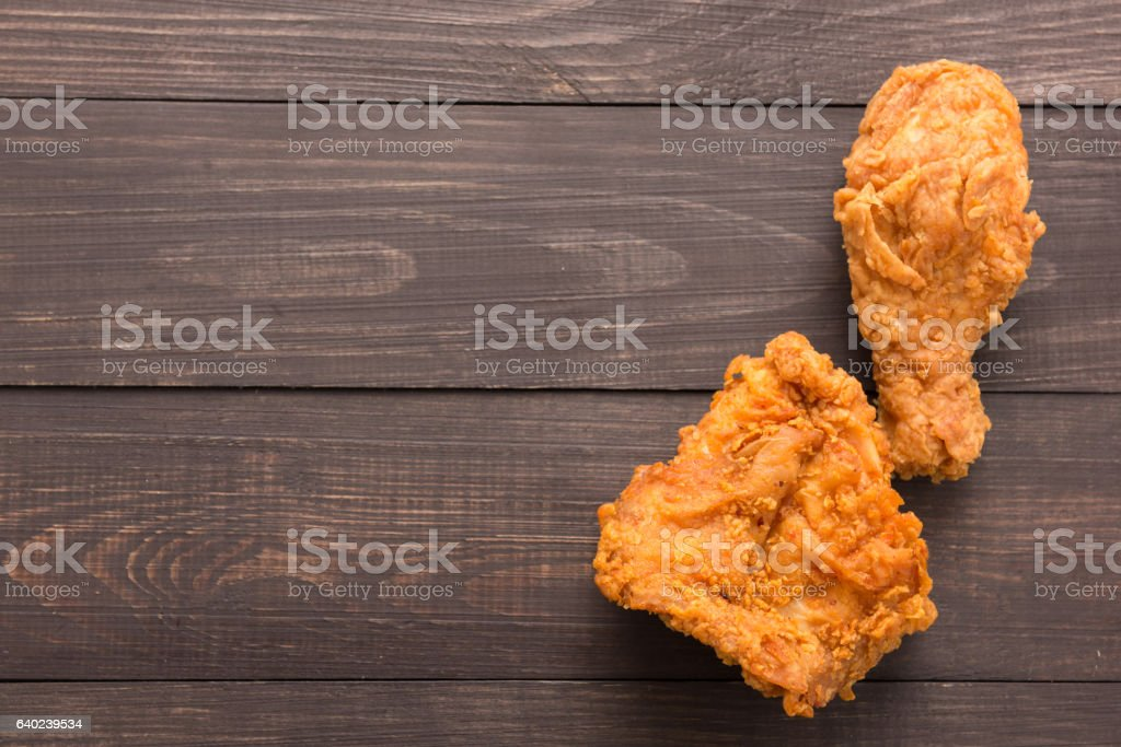 Fried chicken drumstick and chicken breast on the wooden backgro stock photo